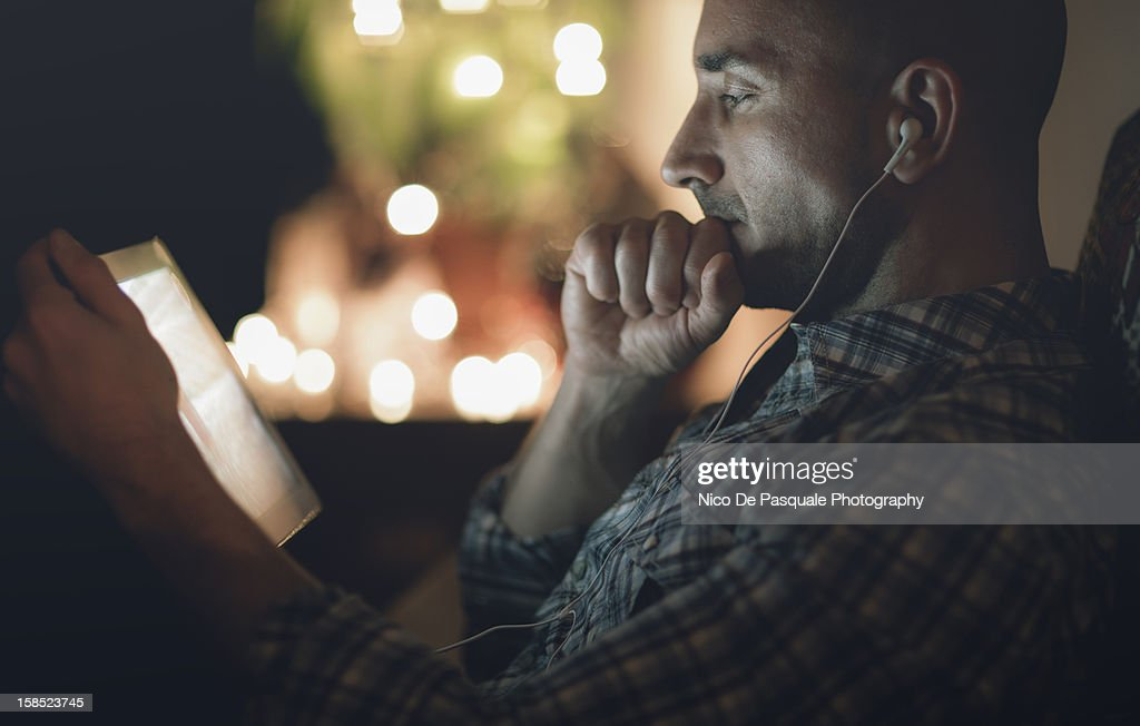 Thoughtful man watching tablet at home at night : Stock Photo