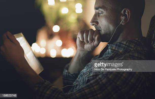 Thoughtful man watching tablet at home at night