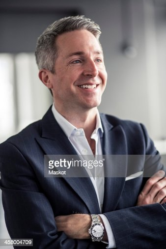Thoughtful mature businessman smiling while standing arms crossed in office