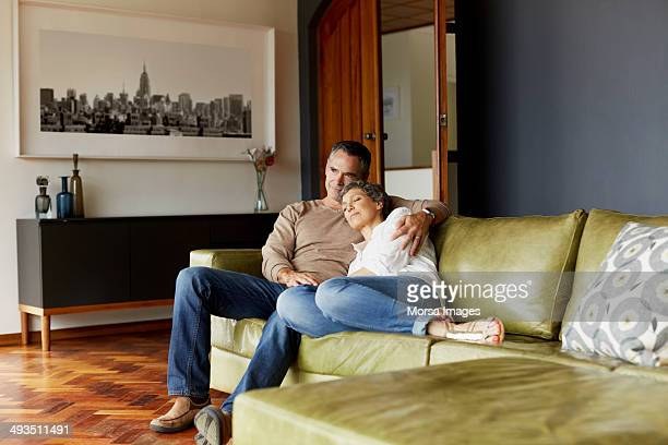 Thoughtful mature couple relaxing on sofa