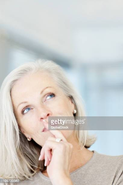 Thoughtful mature woman looking up at copy space