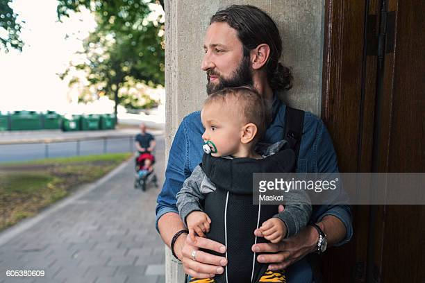 Thoughtful mid adult man carrying baby boy in carrier at doorway