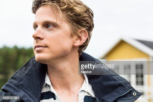 Thoughtful mid adult man looking away outdoors : Stock Photo