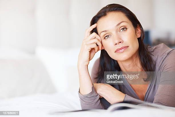 Thoughtful middle aged woman with book - copyspace