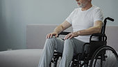 Thoughtful retired male sitting in wheelchair
