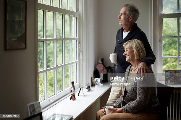 Thoughtful senior couple having coffee in cottage