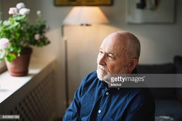Thoughtful senior man looking away at home