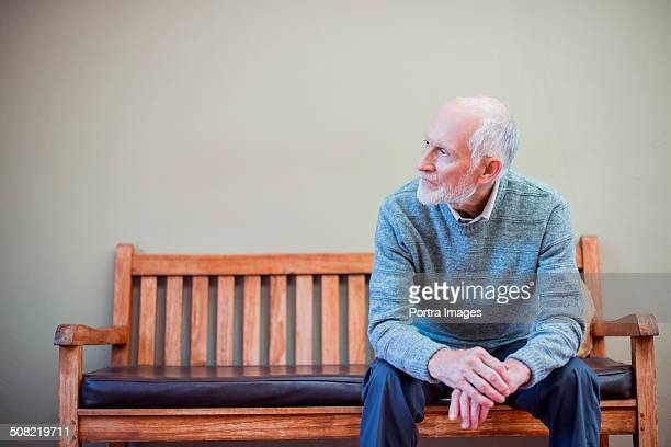 Thoughtful senior man on bench at nursing home