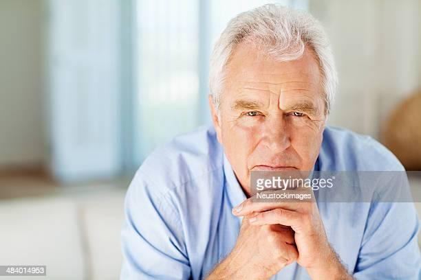 Nachdenklicher alter Mann mit Hand am Kinn wie zu Hause fühlen.
