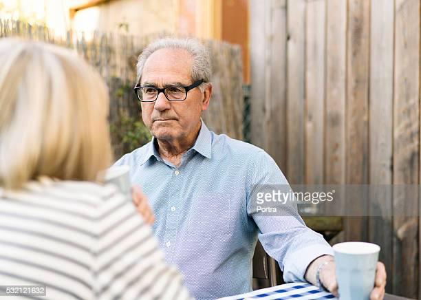 Durchdachte alter Mann mit Frau im Garten