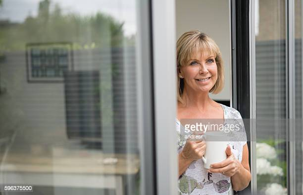 Thoughtful senior woman drinking a cup of tea