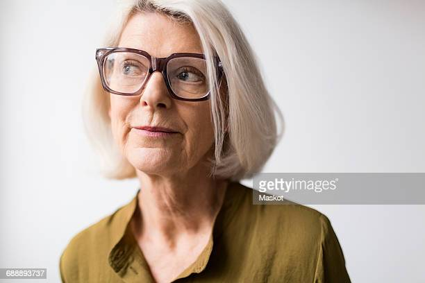 Thoughtful senior woman wearing eyeglasses against white background