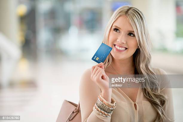 Thoughtful shopping woman holding a credit card