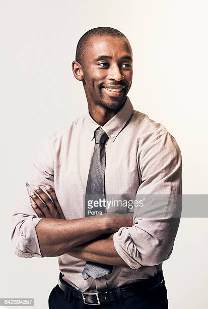 Thoughtful smiling businessman with arms crossed