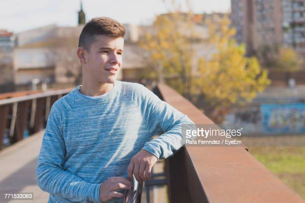 Thoughtful Teenage Boy Looking Away While Standing By Railing