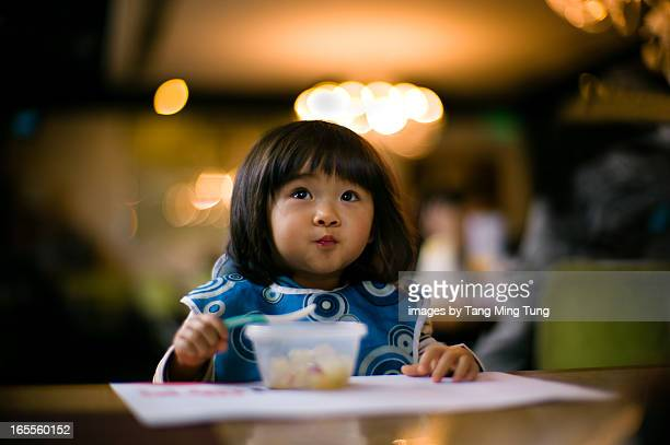 Thoughtful toddler girl feeding herself with spoon