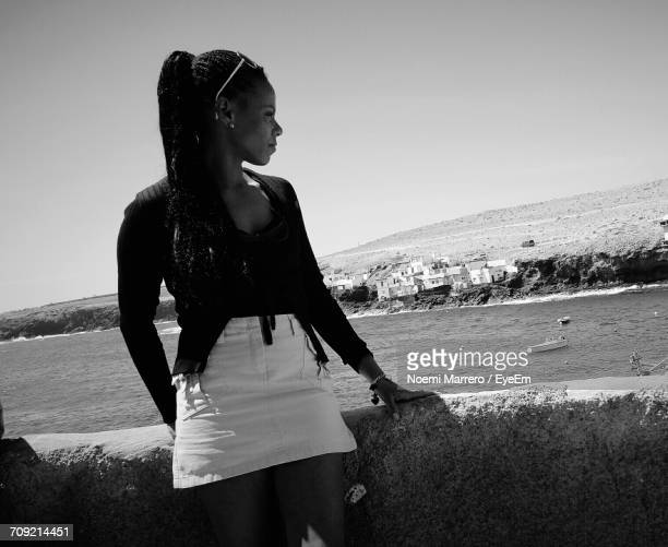 Thoughtful Woman By Retaining Wall Looking At Sea
