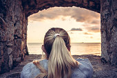 Thoughtful lonely woman devoted into contemplation of beautiful sunset over sea through window of old castle with dramatic sky and perspective view. View from behind. Concept for forecasting and way f
