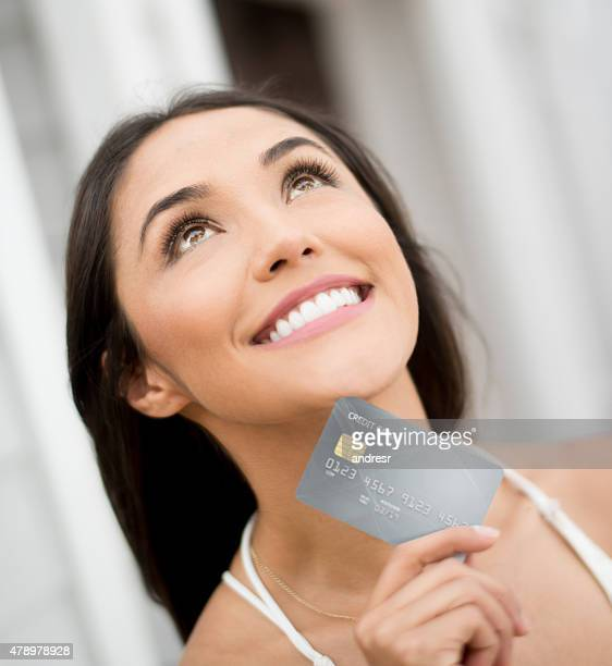 Thoughtful woman holding a credit card