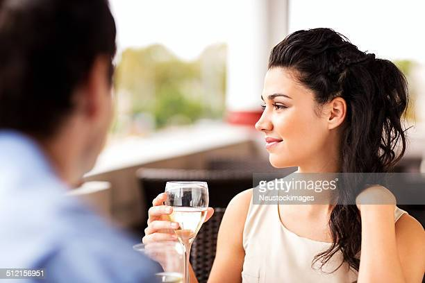 Thoughtful Woman Holding Wineglass Eating Out In Restaurant