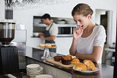 Side view of a thoughtful young woman looking at sweet food at the coffee shop
