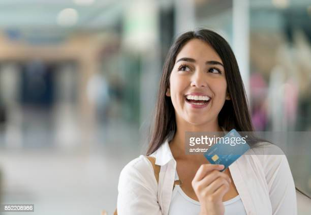 Thoughtful woman shopping with a credit card at the mall