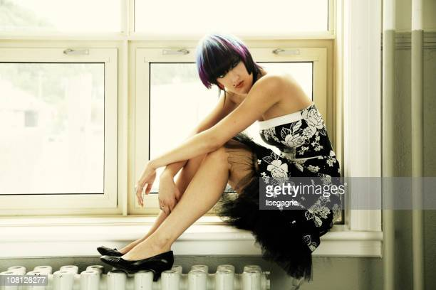 Thoughtful Woman Sitting on Windowsill