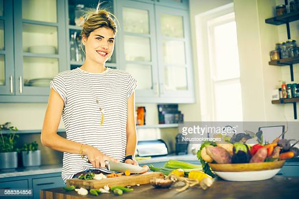 Thoughtful woman smiling while cutting carrot in kitchen