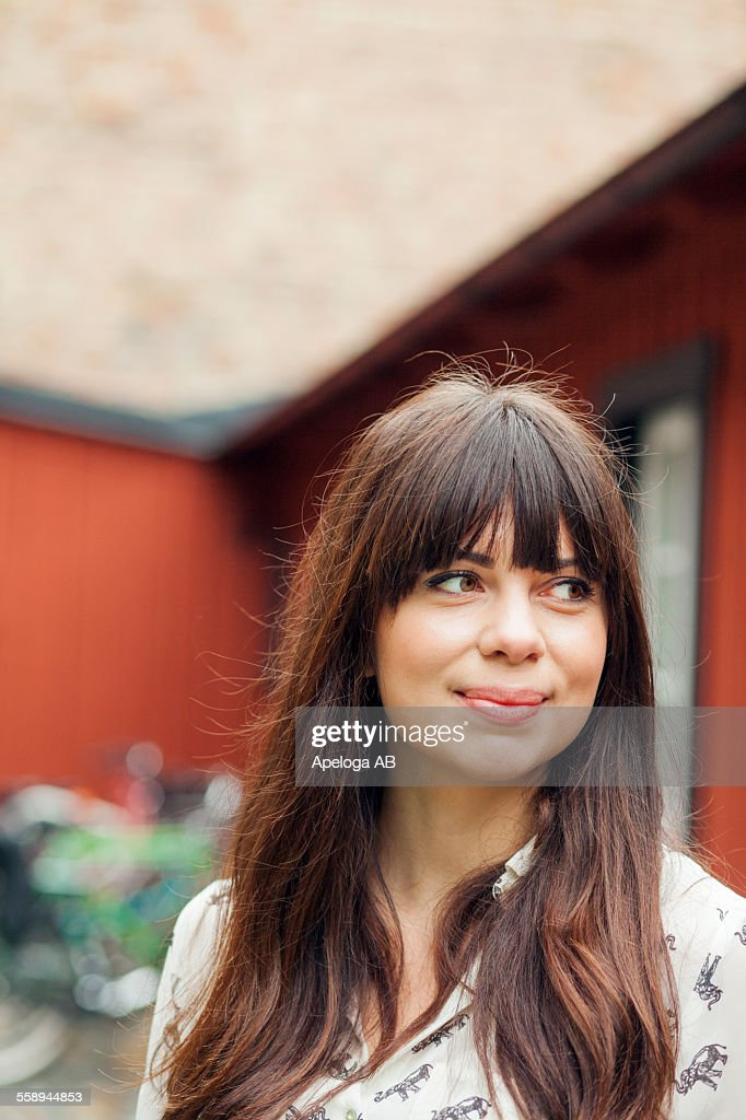 Thoughtful woman smiling while looking away outdoors
