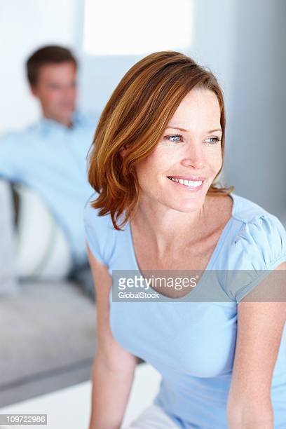 Thoughtful woman smiling with husband at the back