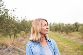Thoughtful woman standing in olive field on a sunny day