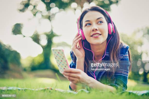 Thoughtful woman wearing headphones while holding smart phone in park