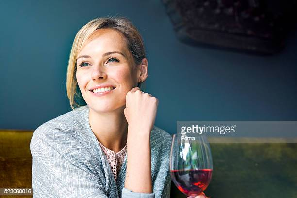 Thoughtful woman with glass of red wine at home