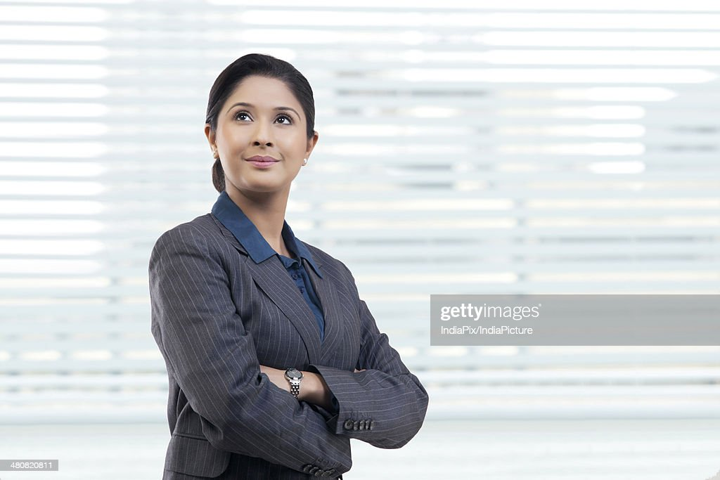Thoughtful young businesswoman with arms crossed looking away in office : Stock Photo