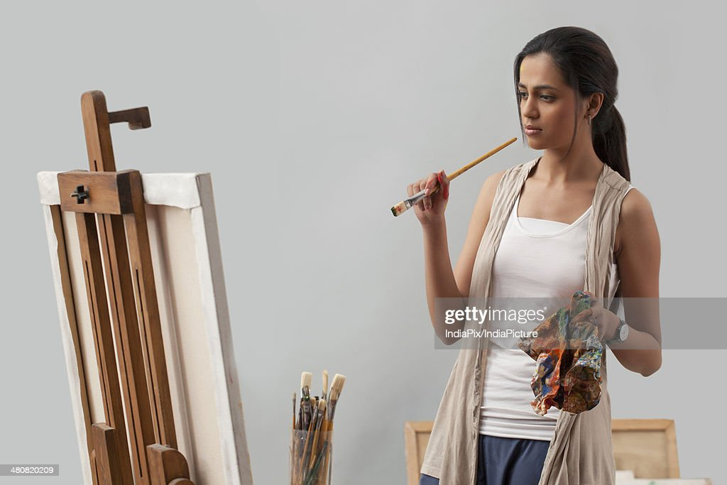 Thoughtful young female artist looking at painting : Stock Photo