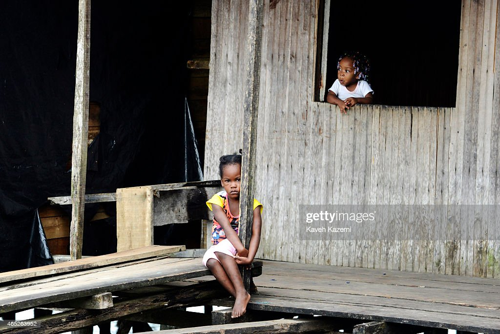BUENAVENTURA COLOMBIA JANUARY 14 2015 A thoughtful young girl sits on a wooden plank walkway outside her wooden house at the end of Puente Nayero on...