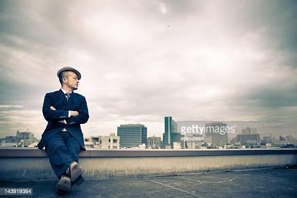 Pensive jeune homme d'affaires japonais avec vue sur la Tokyo et quartier financier