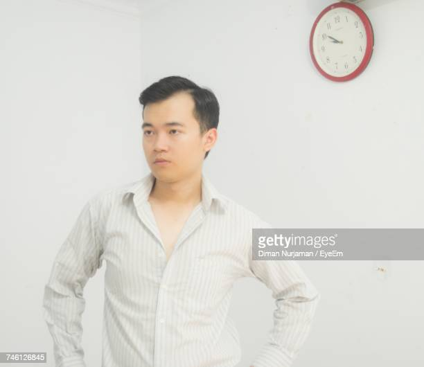 Thoughtful Young Man Looking Away By Clock Hanging On White Wall