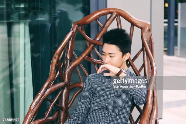 Thoughtful Young Man Looking Down While Sitting In Hammock
