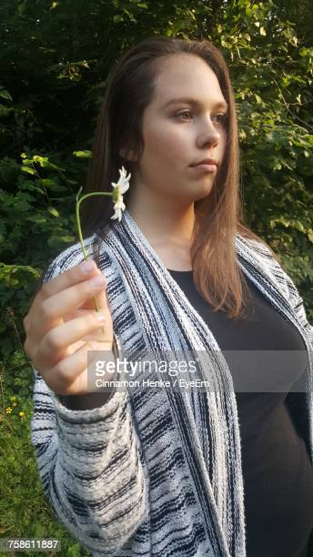 Thoughtful Young Woman Holding Flower While Standing By Plants At Park