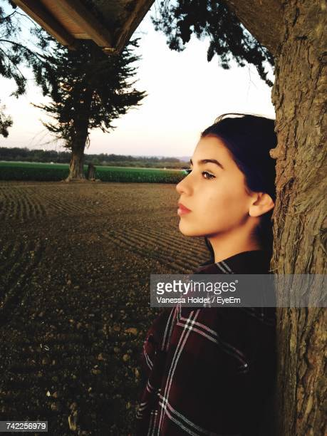 Thoughtful Young Woman Leaning On Tree At Field