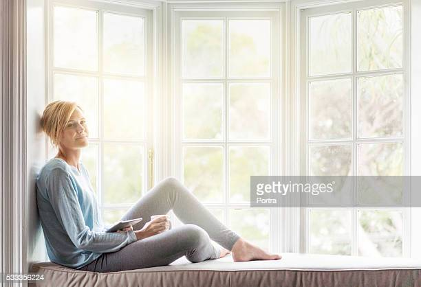 Thoughtful young woman relaxing on window sill