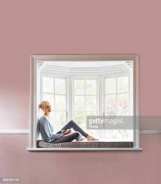 Bien jeune femme de détente sur le rebord de fenêtre