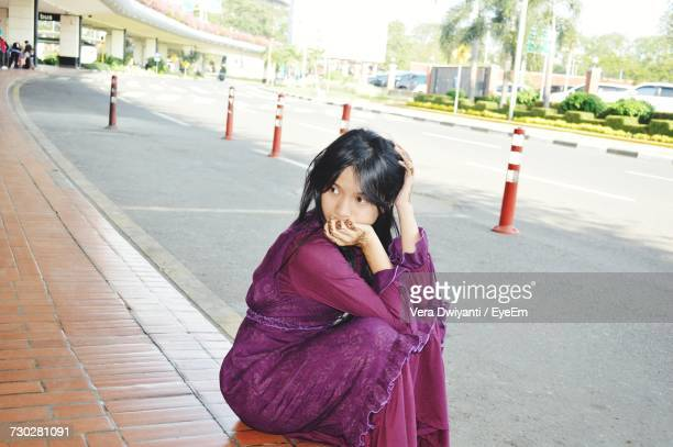 Thoughtful Young Woman Sitting On Footpath In City