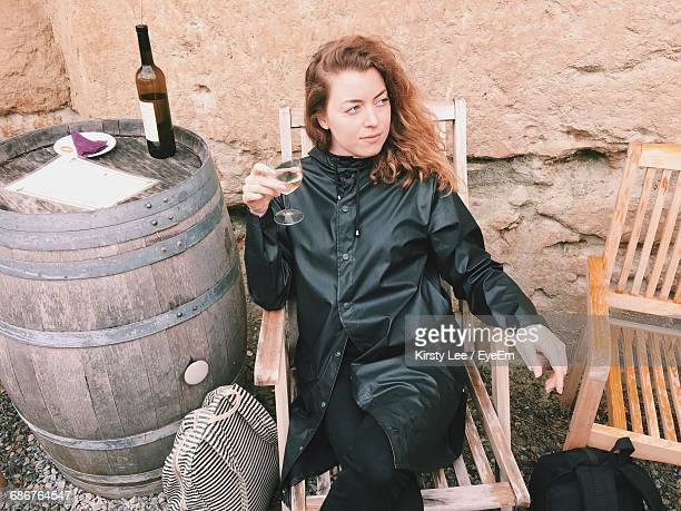 Thoughtful Young Woman Sitting With Wine On Chair By Wall