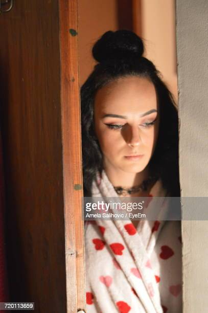 Thoughtful Young Woman Standing At Doorway