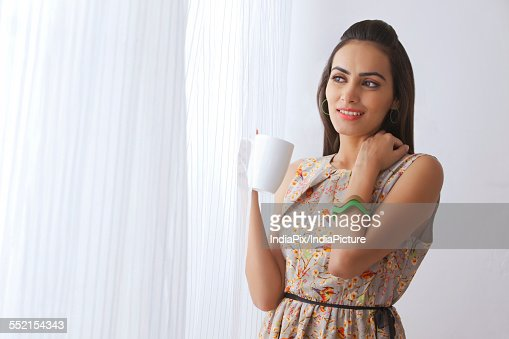 Thoughtful Young Woman With Coffee Cup Standing By Curtains Stock ...