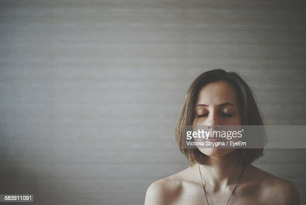 Thoughtful Young Woman With Eyes Closed Standing Against Wall At Home
