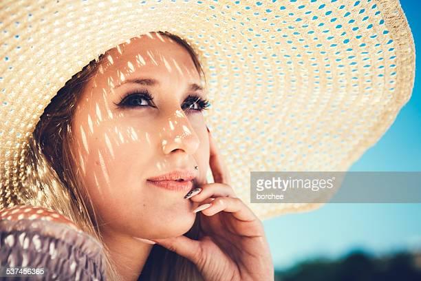 Pensierosa giovane donna con cappello di paglia