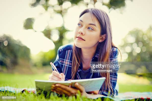 Thoughtful young woman writing in diary while lying at park